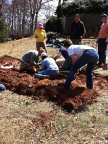 Three people prepare to flip the large sections of sod.